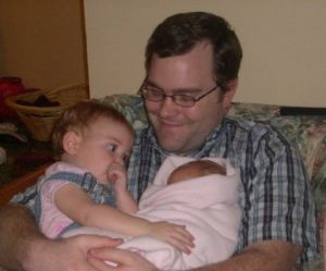 Zachary holding two of his daughters
